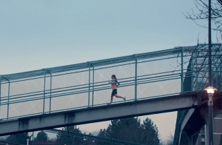 Woman running along a bridge